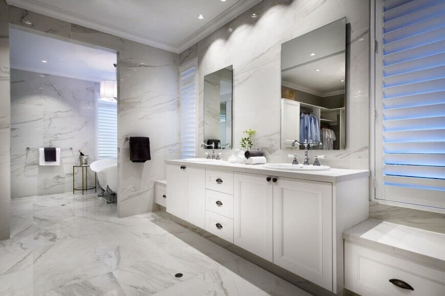 This incredibly luxurious white marble bathroom uses the simple shape and rimless design of the mirrors to highlight the simple elegance of the extensive white marble.