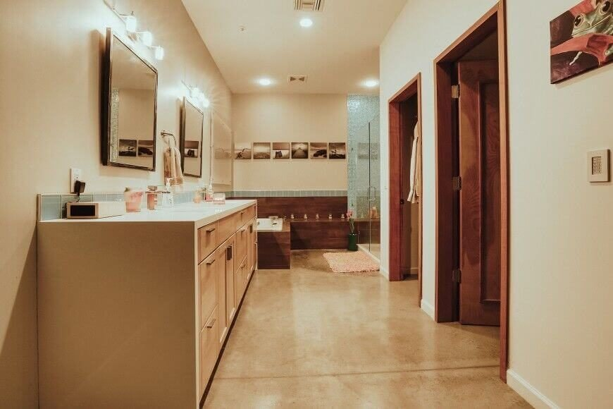 A more contemporary primary bathroom with a large dual-sink vanity with chromed mirrors. The bathroom continues around the corner as a low-profile wood-enclosed soaking tub and a glass-enclosed shower in the corner. A series of photographs along the far wall are in a light sepia, which complements the dark wood and light beige.