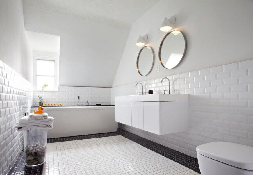 Subway tile is a classic element that adds style and class to any style of bathroom. In this one, it contrasts with the smaller square tiles of the floor. Tiling the majority of a bathroom also has a practical side; it prevents mold, mildew, and other water damage to the walls.