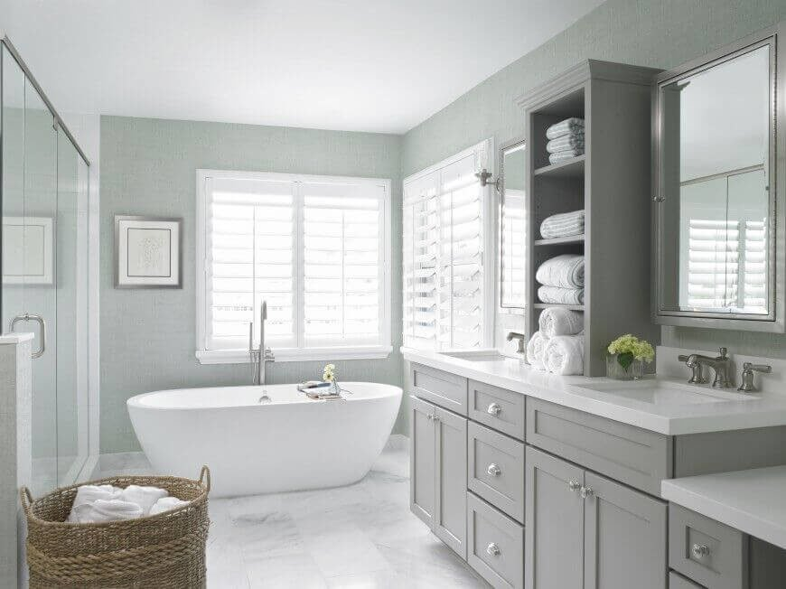 Subdued blues and grays are matched with pristine white floors and countertops for a relaxing, subtle space that's easy on the eyes. The free-standing soaking tub and built-in wooden shades add to the contemporary class. Open shelving separates the two mirror-fronted medicine cabinets atop each sink.