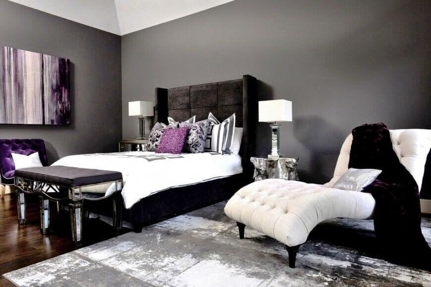 The white furniture in this room creates a striking contrast to the black, grey, and violet color scheme seen here.