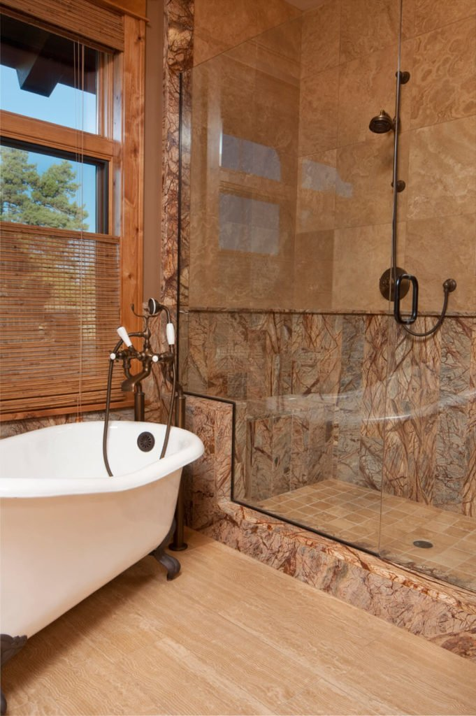 Intricate texture on the outer shell and inside of the shower give this bathroom space its character, and certainly draws in the eye. The rich wood window frame compliments the stone, while a clawfoot tub sits at an angle below the window.