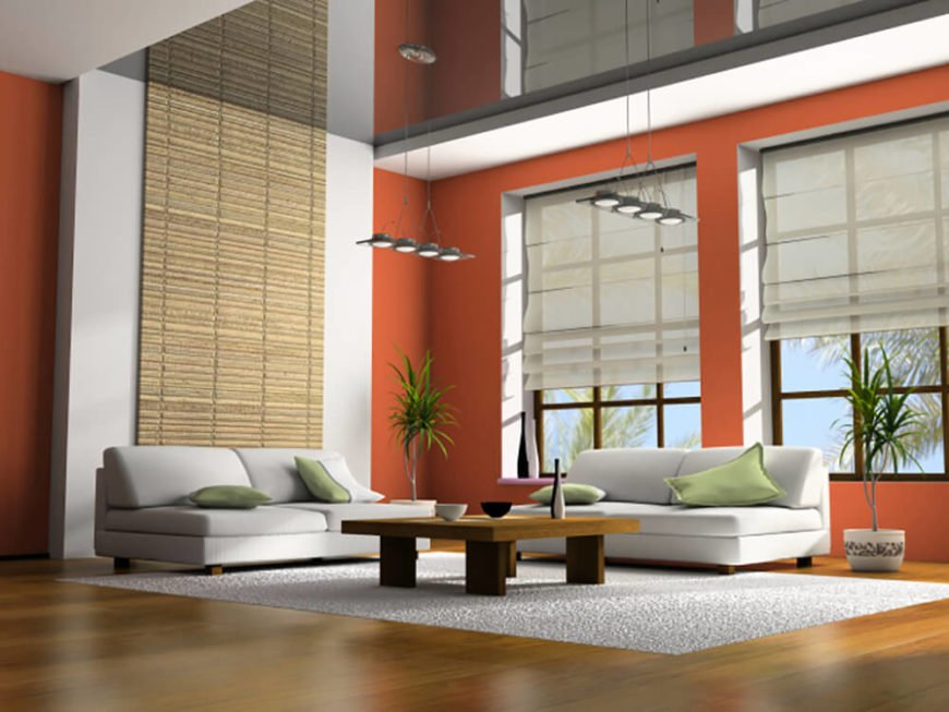 Green plant life stands out well against the bright orange walls and the white furniture of this room.