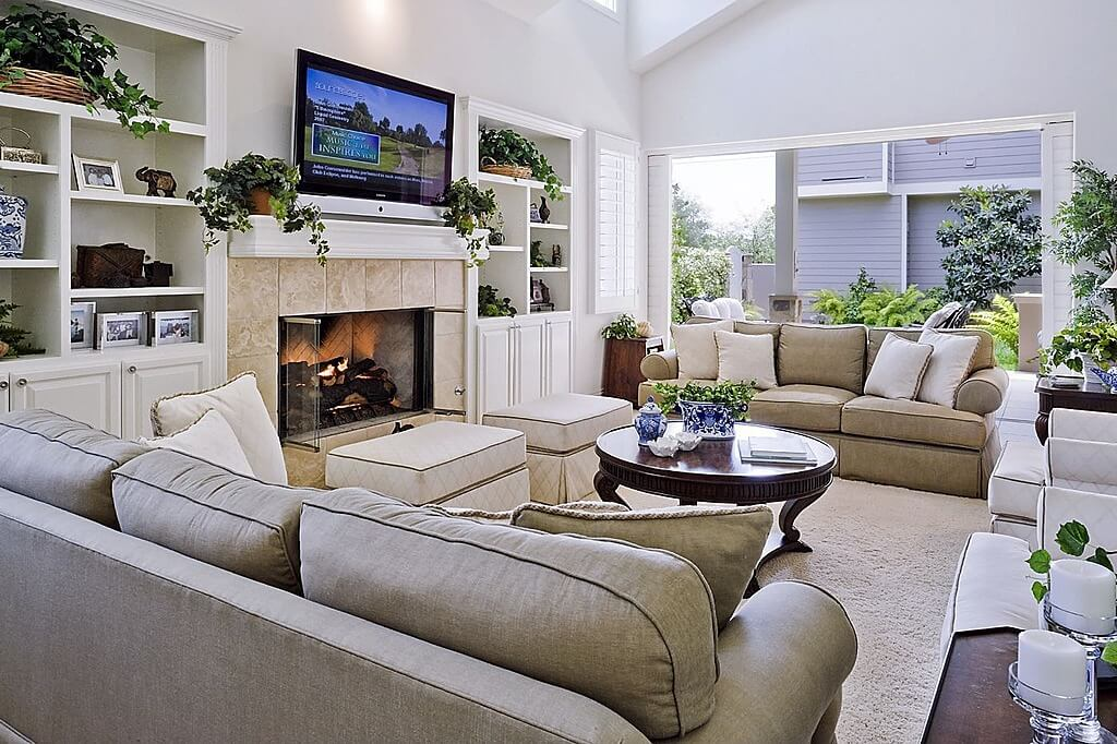 The inclusion of plants in this room marries the indoors with the outdoors and creates one seemingly unified space with the sliding doors open. The tan color scheme of the room allows the plants to pop out of the background, as well as the accents of blue china.
