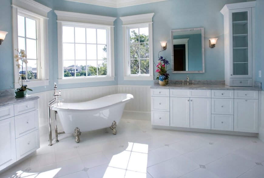 The corner of this bathroom is well lit by natural light flooding through the three paned windows. A clawfoot tub lies beneath and is accommodated by stainless steel hardware. This space is framed by two matching counters in this light and bright bathroom.