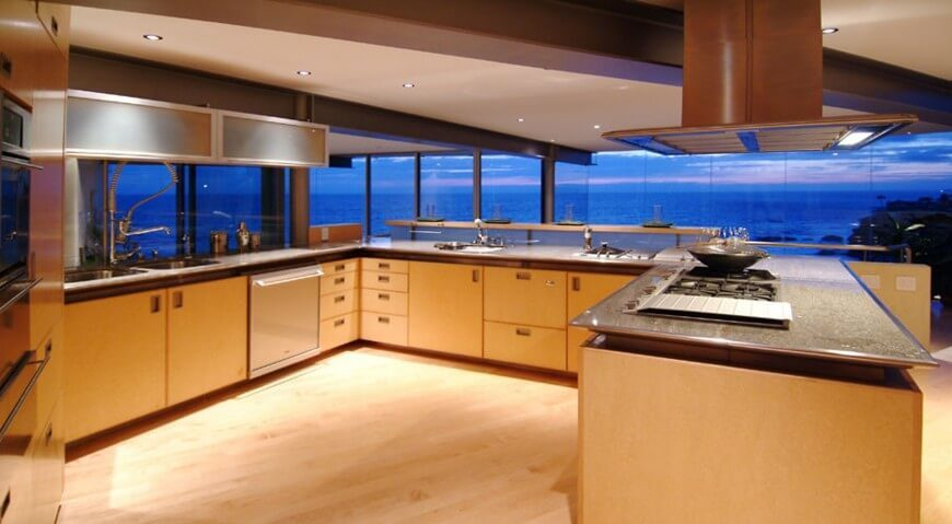 This space is set in the back of a room, with the dining area separating the kitchen from the large floor to ceiling windows. The bright lighting in this space creates a contrast of light between the interior of the home and the horizon, which contributes to a luxurious tone set in this kitchen.