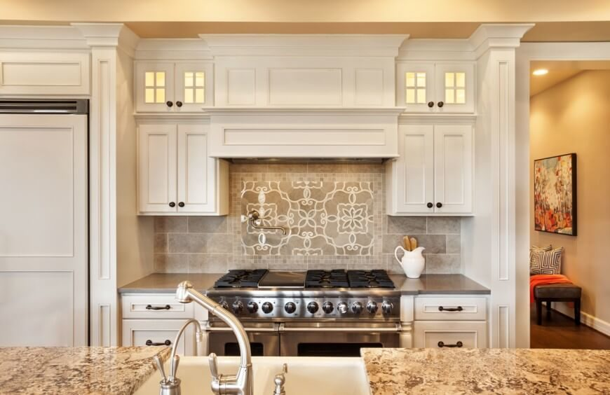 Stark white cabinetry is complimented by a light grey tile backsplash and rich textured granite countertops in this kitchen. The unique design in the tile behind the stove helps to break up the pattern and accent the space subtly.