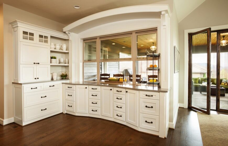 In this kitchen space, rich stained wood flooring meets white cabinetry and creates a strong contrast in the space. This counter features a framed opening connecting to the eat-in counter and dining room.