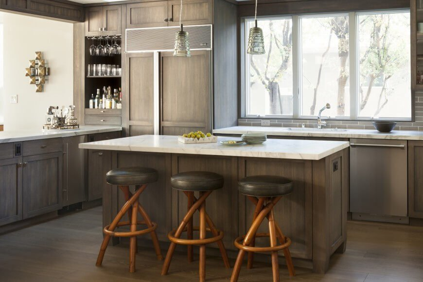 This kitchen features contrasting colors due to the white marble countertops above the dark stained wood floors and cabinetry. The chairs pushed in to the eat-in counter are made up of twisted bamboo-like sticks. Their gloss and design draw in the eye and help to accent the space.