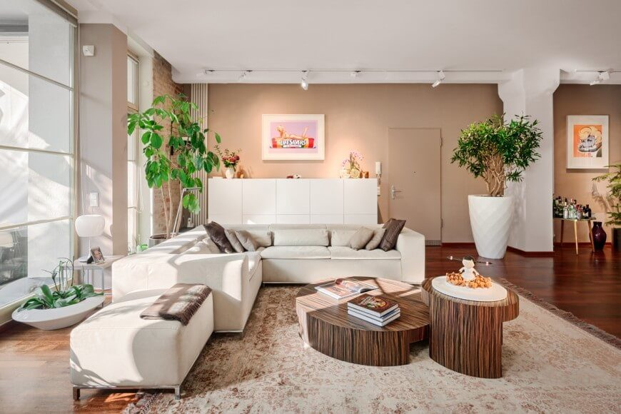 Setting the base of the room as white with accents of tan, brown, and gray creates a great showcase for both the bright green plants and the stunning wood floor. The interlocking coffee tables work to bring together the different shades of brown and tan.