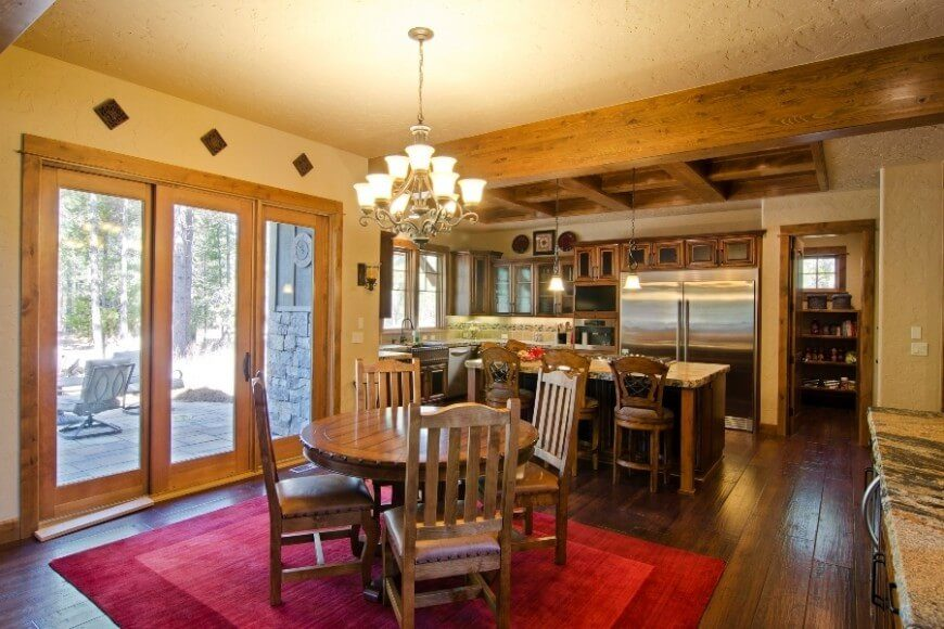 This kitchen shares a space with a dining room, and the bold red rug covering the hardwood floor in the dining room helps to create a division of the two spaces. An island with an eat-in counter also helps to divide the space. Wooden rafters on the ceiling and the amount of wood grain contributes to a theme for the kitchen.