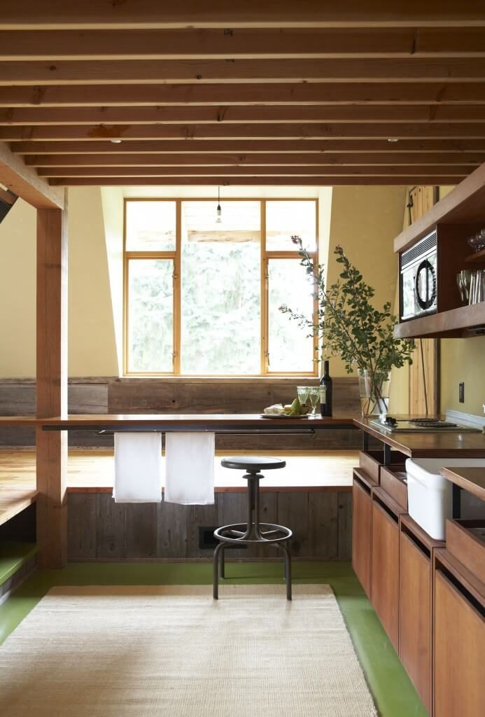 This kitchen sits at a lower level than the surrounding room and features a unique green floor. The light pouring in from the windows reflects off the glossy hardwood floors around the kitchen. Within the lower level, there are rich wooden cabinets, and small kitchen appliances.
