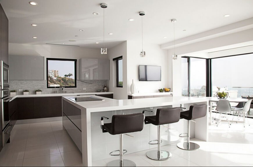 A modern kitchen with a sleek and futuristic design, this space has a tone that is set by the white glossy surfaces, and accented by the black framing around the windows and on the chairs pushed up to the eat-in counter.