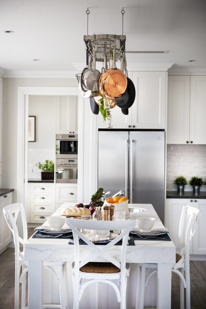 This contemporary kitchen features a white marble countertop on the island, with an eat-in extension set for three people. The white walls and cabinetry help to keep the space looking clean and crisp, while black counter tops and chrome appliances help to contrast and balance the space.