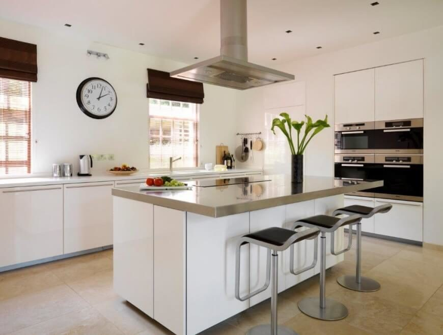 Large square tiles make up the flooring, with large white cupboards featured on the counters in this kitchen. A large glossy top island is centered in the space with modern bar stools pushed up to the eat-in counter.