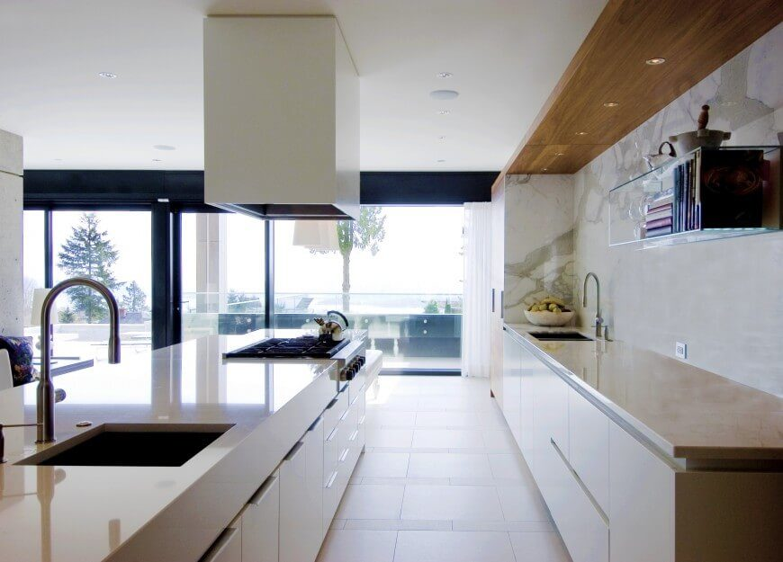 A glossy countertop covers the large island, which is complete with a stove and a sink. The counter opposite of the island sits against a marble stone wall, also featuring a large sink. This kitchen has plenty of space and is well lit by the natural light spilling in through the floor to ceiling windows.