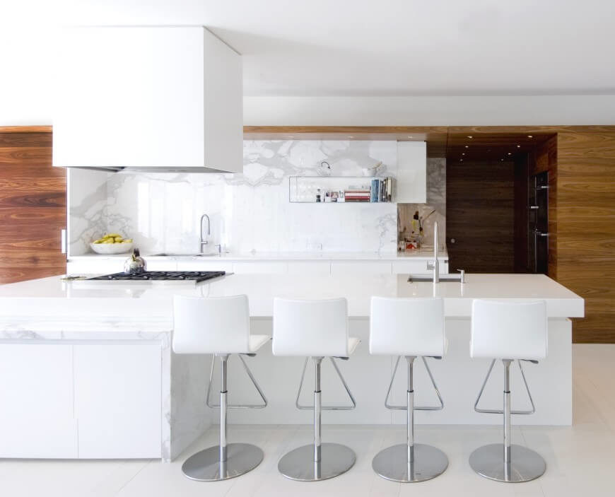 A stark white color scheme is prevalent in this kitchen, with a light marble island top and countertop backsplash running from the countertop to the ceiling. A woodgrain paneling covers the walls around the kitchen and offers a contrast of color to the monochromatic design.