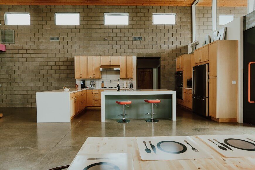 This kitchen is set against a plain brick wall, with high ceilings and an open design. An L-shaped counter forms one end of the kitchen and is complete with plenty of cabinetry. An island is centered in the kitchen space, featuring an eat-in counter. The other side of the kitchen features large appliances and more cupboard space.