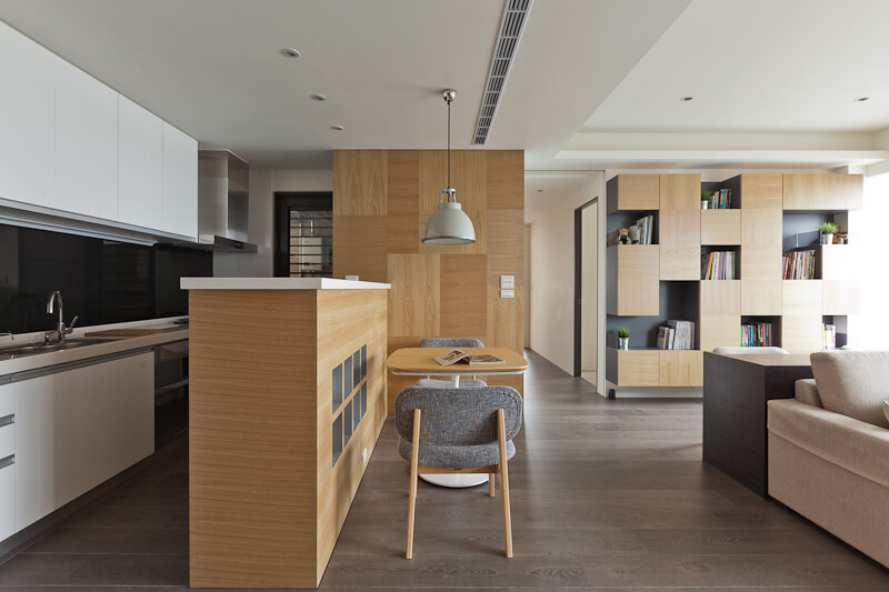 The soft wood grain in this kitchen helps to set a relaxed tone for the space. The contrast from light golden wood to dark stained wood for the floor creates a balance in the space, suggesting sophistication. A small coffee table is featured next to a high counter. This space is lit by natural light from the adjacent room.