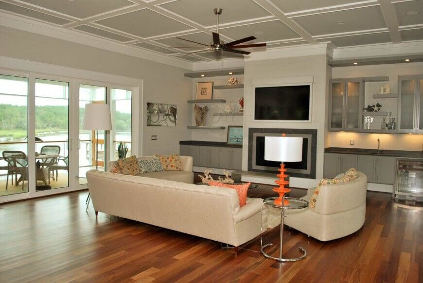 This cottage-styled living room has a large fireplace that is perfect for adding a bit of light to the room. A television is built into the wall for a flat and flawless surface.