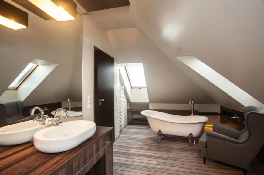 This bathroom is located at the top of the house, as you can tell from the angled ceiling. Multiple skylights let in natural light, which illuminates the rich stained hardwood floor and counter.