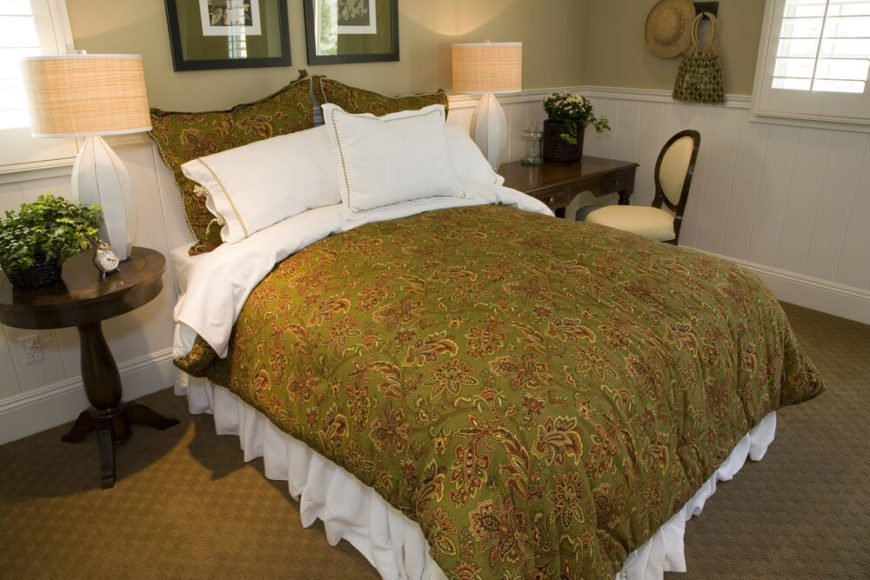 Decorative pillows create the headboard in this room, as does the white paneling on the bottom half of the wall. Highlighting the green and tan colors of the room with bright white and dark wood accents makes for great contrast.