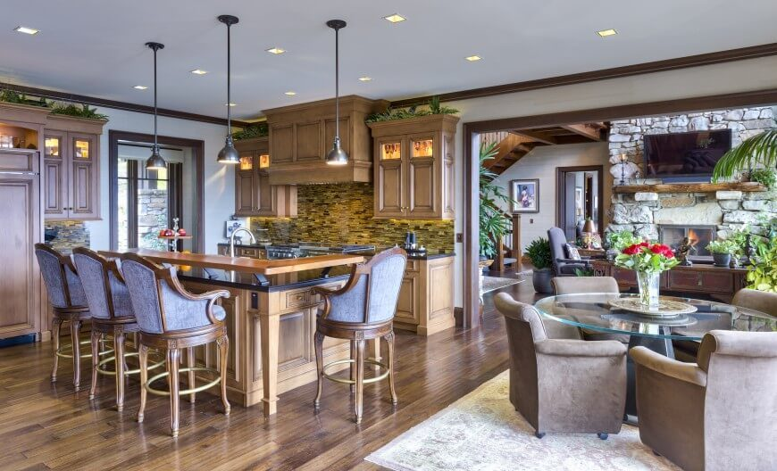 Covered in rich wood, and featuring intricate detail, this kitchen is refined and comfortable. The large island has an eat-in extension with upholstered stools for seating. Behind the stove and countertop there is a textured tile that accents the space and draws in your eye.