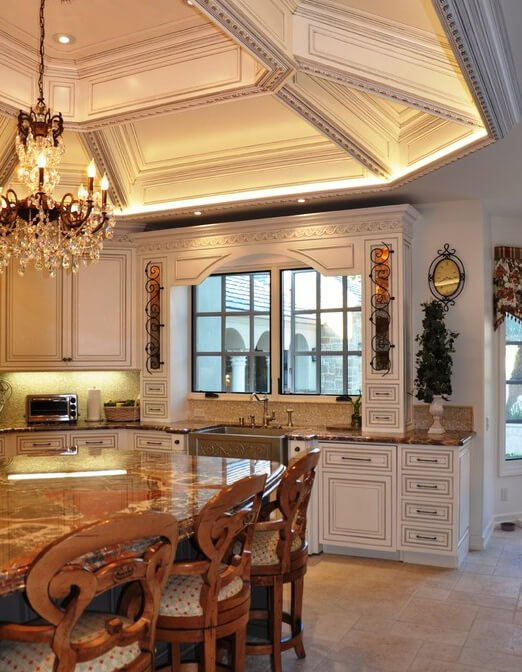 The vaulted ceiling and hanging chandelier give this kitchen a regal atmosphere, with detail on the cabinetry and a unique texture on the dining table as contributing factors. The space is well lit by artificial light, but also features large windows to let in the natural light.