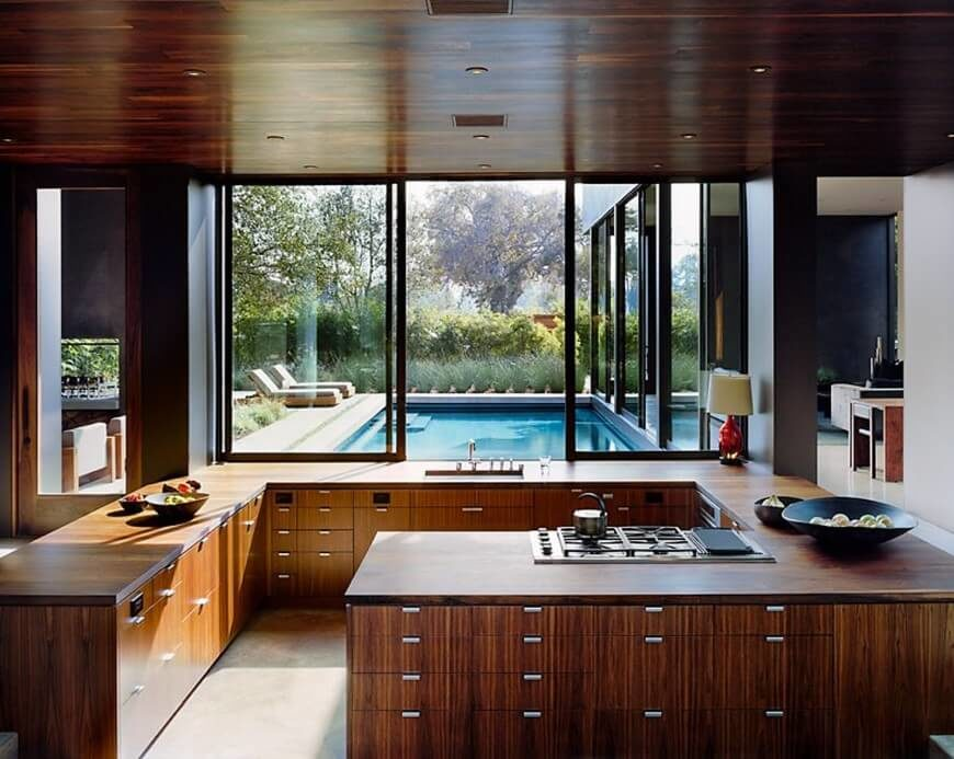 Richly stained wood covers this kitchen, from the drawers and cupboards in the G-shaped counter, to the ceiling above this space. Beyond the sink, large sliding windows open up to a pool area and patio.