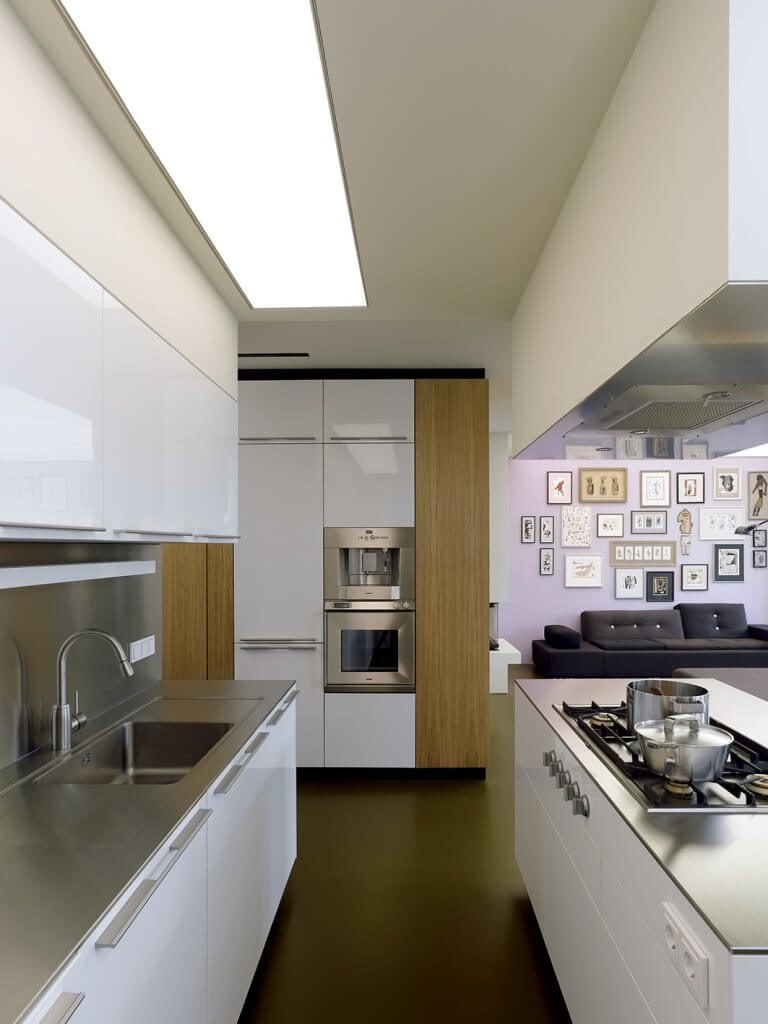Glossy floors and countertops help to reflect light in this kitchen and create a modern look. The island features a stove top and the opposite counter features a large sink, making it an efficient work space. Natural wood accents help to balance the sleek and modern atmosphere.