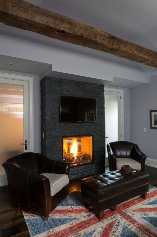 This dark stone mantle contains a roaring fire for a peaceful reading area. A television is mounted above the fireplace for a quiet rainy day by the fire.