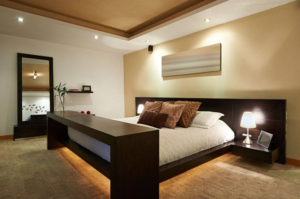 The unique lighting in this room creates a calm atmosphere, while the bed sits centered in the space. The color of the vaulted ceiling is complemented by the accent wall and the carpet.