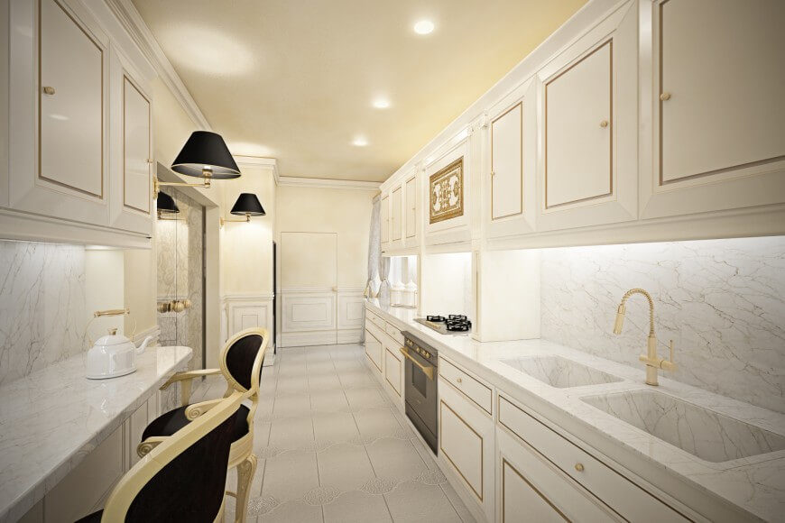 This white kitchen features gold detailing that suggests refined living. The creamy walls and ceiling offset the stark white cabinetry just enough to amplify the gold detailing and compliment the entire space.
