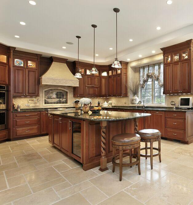 Gorgeous cabinetry is offset by creamy walls and subtly green granite counters. The bright floor helps to reflect plenty of lights around the room and silver accents add a touch of modern.