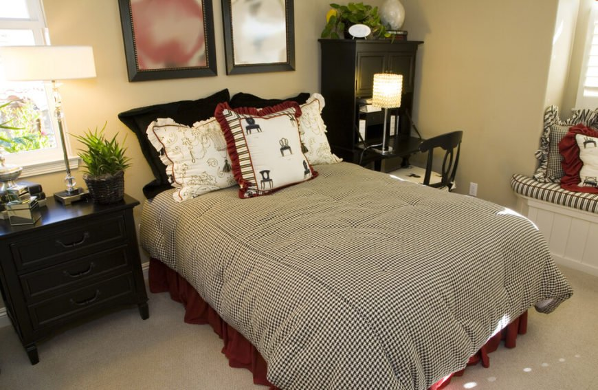 The black, white, and red color scheme of this bedroom against the plain beige backdrop adds enough interest to this room that it does not need a bold headboard.
