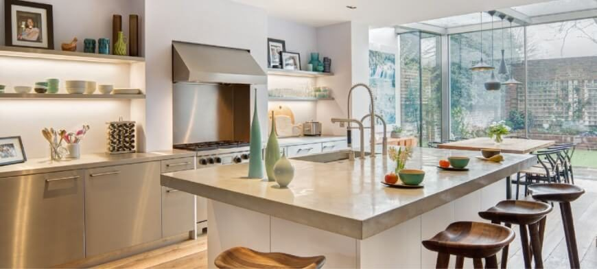 This kitchen is decorated with pastel colored vases and other kitchen utensils. The space opens up to a dining room with glass walls and allows plenty of natural light to shine through into the kitchen. A large island in the center of the space features an eat-in counter with stained woodgrain stools.