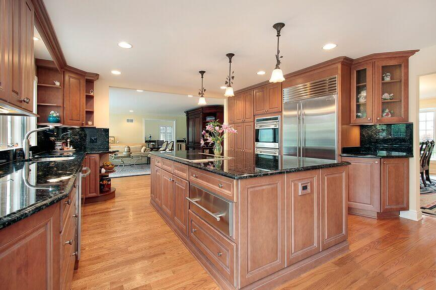 Marbled dark granite is lovely against the muted brown of the cabinets. Glass fronts and open shelving break up the expansive cabinets and create some nice visual difference. Shining stainless steel is carried through the kitchen by the appliances and cabinet hardware.