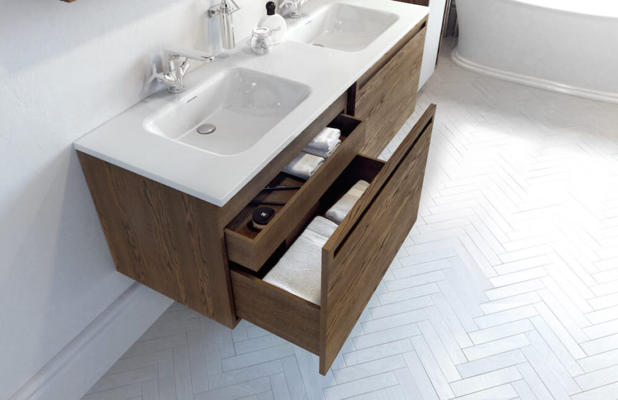 From this angle we can see inside the vanity's ample storage drawers. The sleek front is achieved by concealing a shallower drawer behind the bottom drawer's front facade. The bottom drawers are deep enough to store extra linens or hair products!