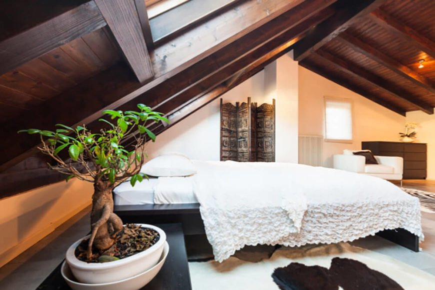 With a steeply pitched ceiling it can be hard to incorporate a headboard. Leave it out entirely and utilize a free-standing bed frame like this one. The contrast of black furniture against the dark brown woodwork and white backdrop creates a uniquely and simply designed space. The bright green of the small tree in the foreground acts as the only bold color in the room.