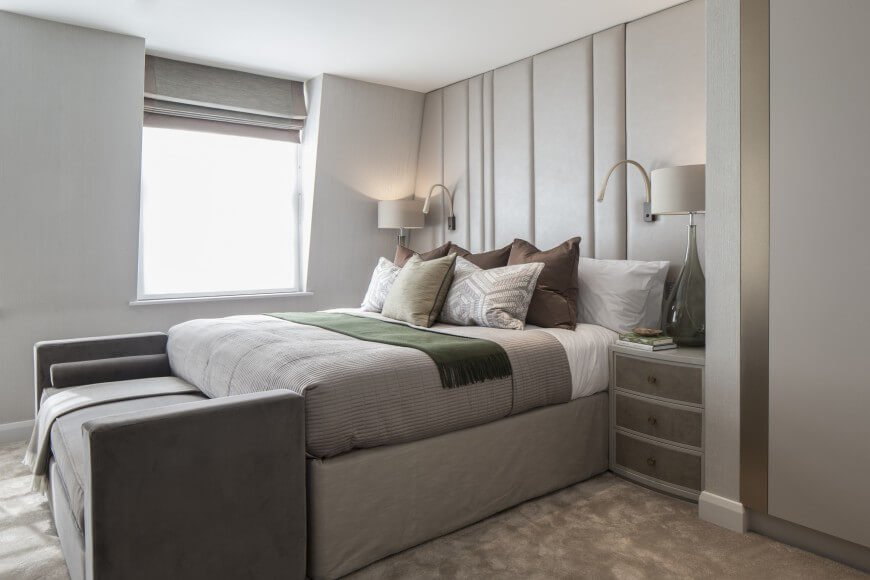 A cushioned accent wall does the job of a headboard while also creating interest for the rest of the room. Making use of the suede texture throughout the room add to the softness of the room. The neutral color palette is livened up by the olive green throw over the bed.