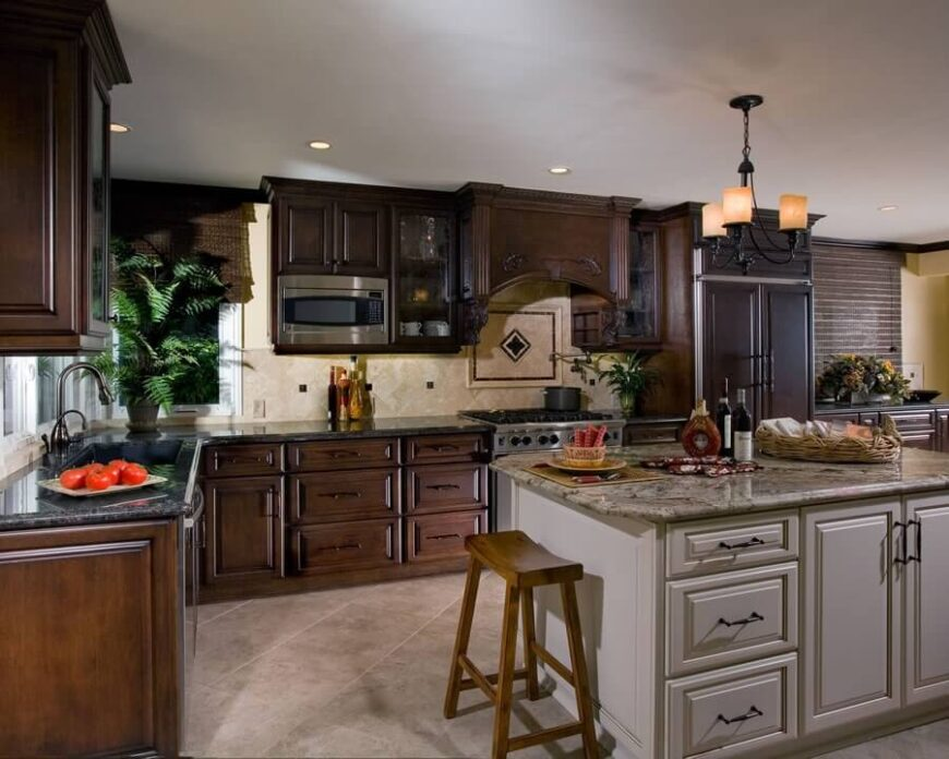 To offset the depth of the dark cabinets and equally dark grey counters, the island has been comprised of white and light shades. Warm, off white tile and cream walls brighten up small sections of the room.