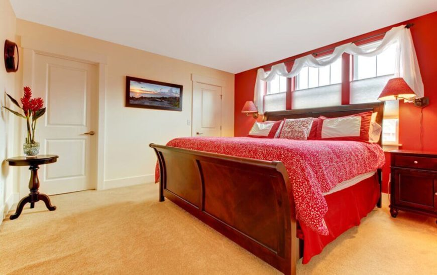 Bold red colors accent this bedroom, while the light colored walls and carpet balance the space. The large bed sits high in the room , and is framed by windows behind the headboard. Two lamps on either side of the bed create a symmetrical effect.
