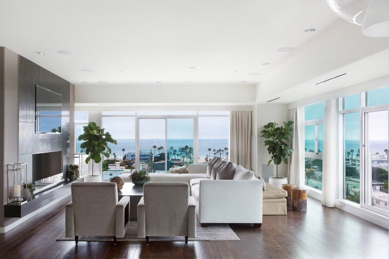 Brilliant white is toned down with splashes of muted gray and accents of silver while the inclusion of greenery accents the use of natural woods used in the room.