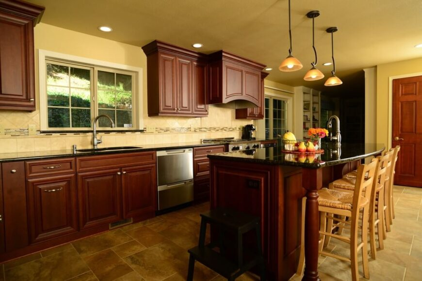 Dark cabinets and counters are balanced by the use of pale colors in the walls and floor. Contrast tile work can be seen in backsplash that helps to pull the colors of the tile floor into the design. Glossy black granite counters make for a striking sight against the red hues of the cabinets.