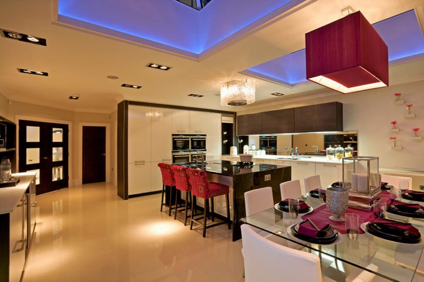This kitchen shows of two different types of recessed lighting - the ambient blue lighting and the smaller can lights in the ceiling. These can lights create pools of light around the kitchen while the blue lights create an interesting visual when viewed against the burgundy color scheme of the rest of the room.