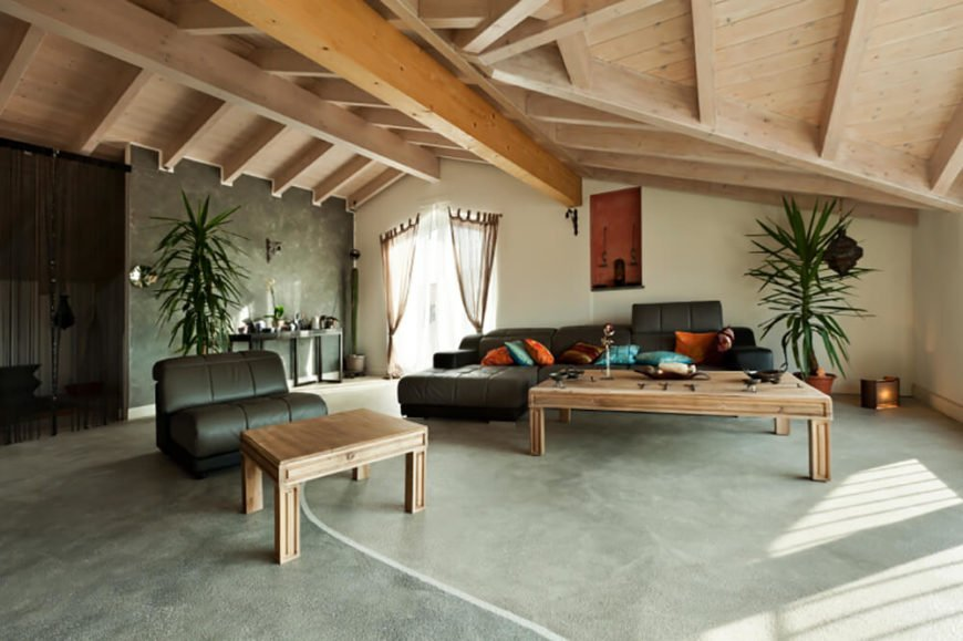 Pale raw wood and concrete floors make this space feel stark and open, but the addition of chocolate brown furniture and bright splashes of orange, teal, and green warm the room and counter the cold feel of the base materials.