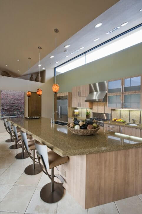A kitchen with an enormous island that features eating for at least five at the island. The island also plays host to a dual basin sink.