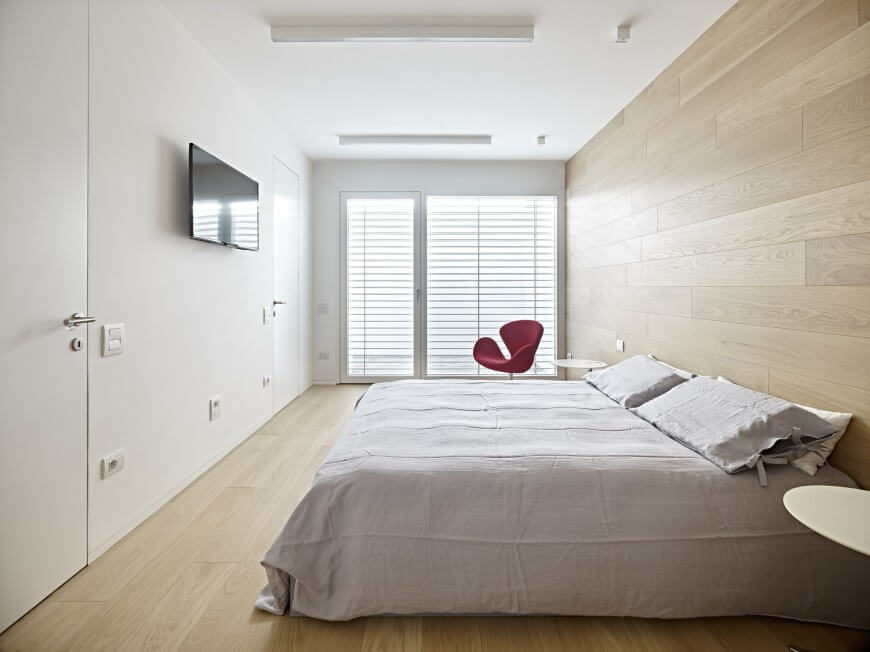 Instead of a headboard, this gorgeous wood accent wall carries the wood floor up to the wall and highlights the simple bed and furniture choices. This minimal design would be taken away from with a clunky headboard included in it.