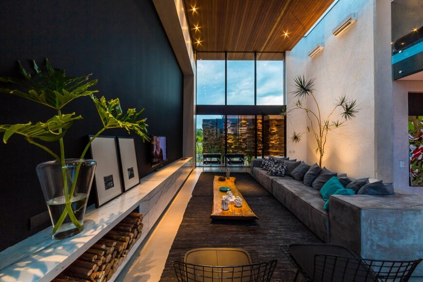 Here the plants work with the design to accentuate the style of the room. Rich textures fill the space with interest and bright colors create a cozy feel in this otherwise large open space.