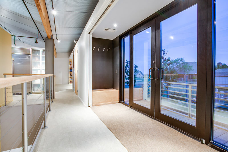 The foyer of the house is located on the second floor. Large windows and massive front doors lend to the open-concept design of the second level and features a mix of dark wood and the pale oak used throughout the rest of the design. Coat hooks and a built-in bench can be seen next to the door.